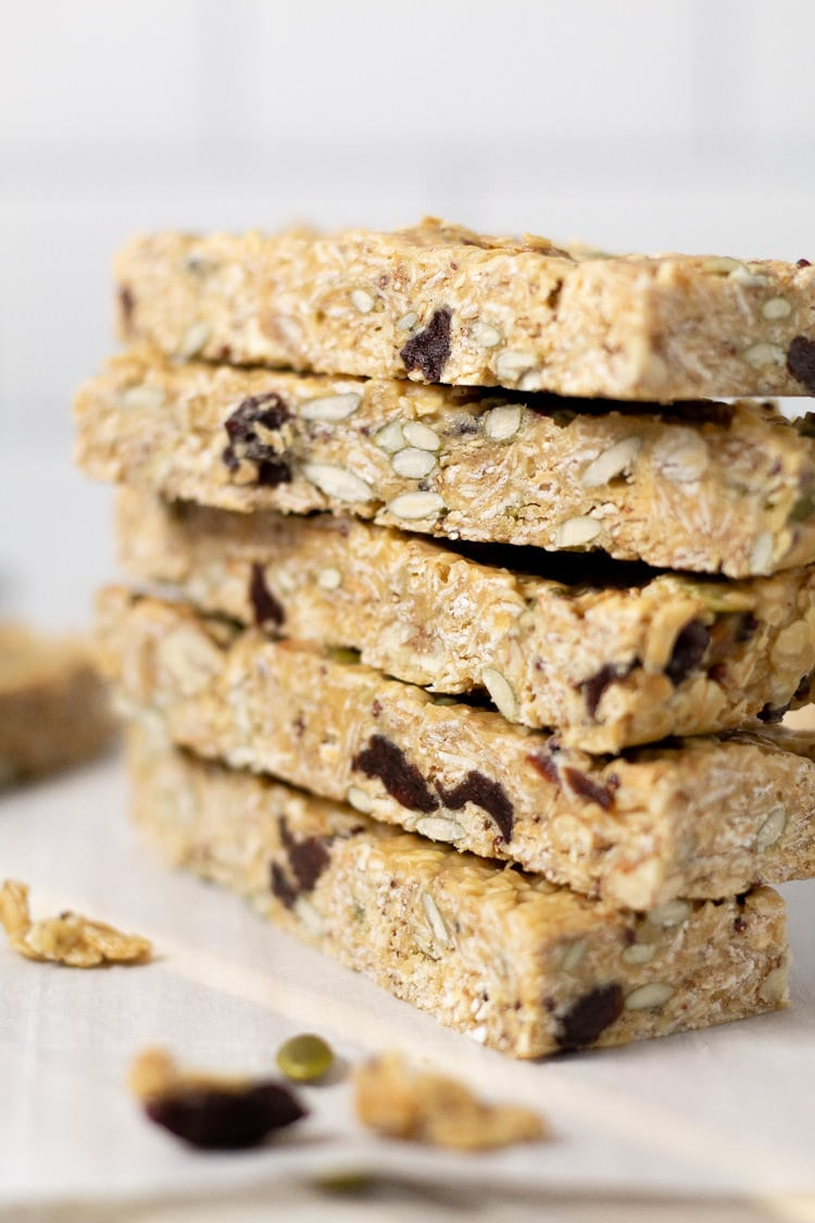 Homemade chewy granola bars stacked high on the counter
