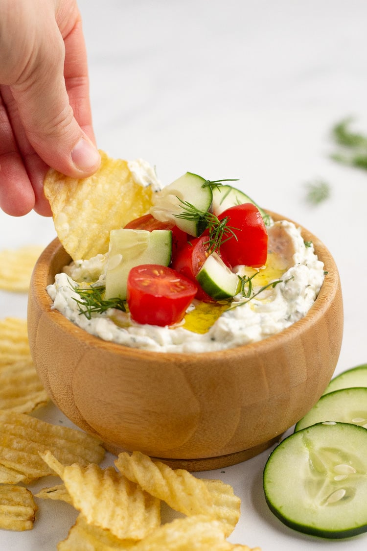 Wooden bowl filled with Mediterranean Dip with a hand dipping a chip into the dip