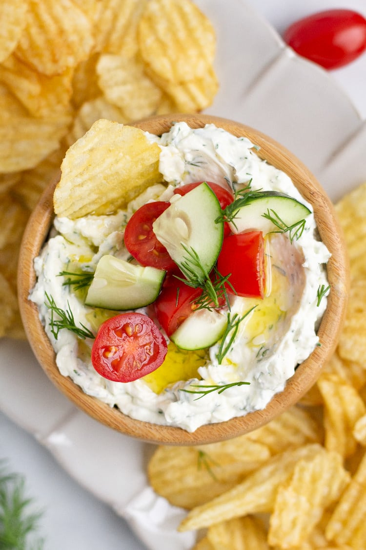 Overhead shot of a wooden bowl filled with creamy Mediterranean dip on a platter of potato chips