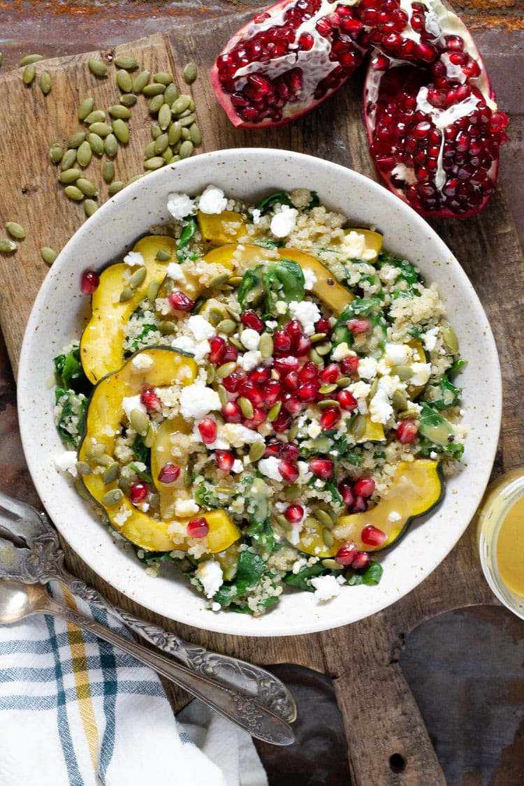 Bowl of squash quinoa salad with pomegranate seeds and goat cheese