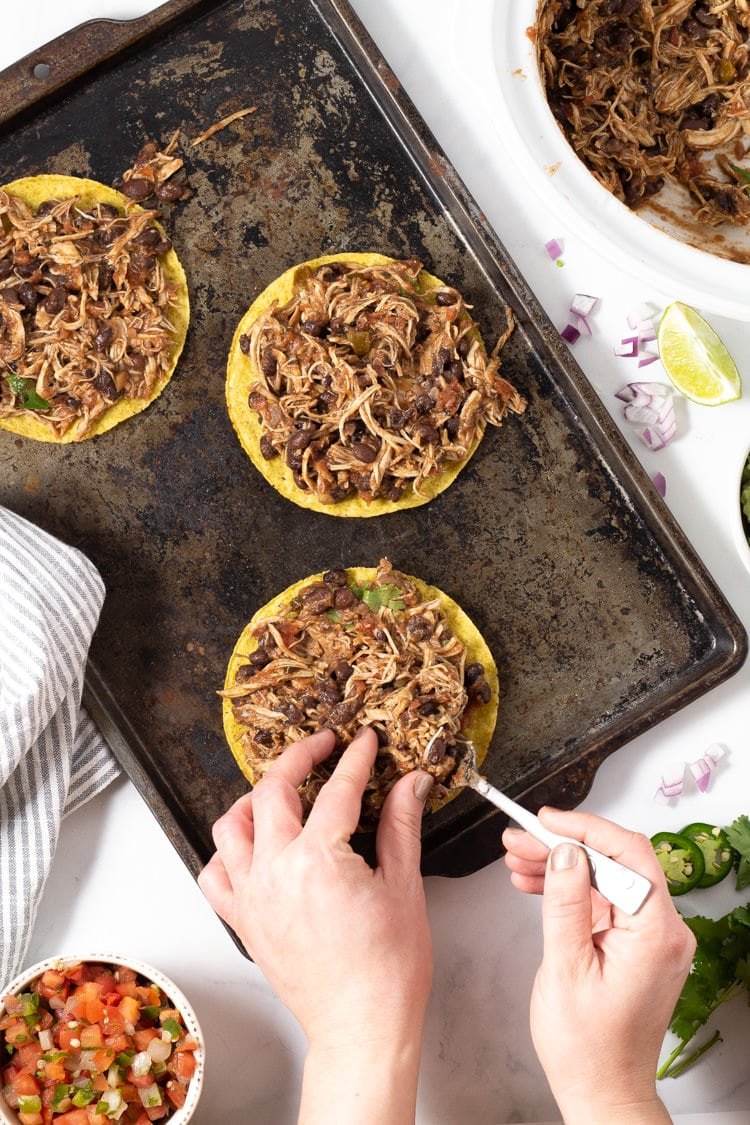Overhead shot of two hands assembling chicken tostadas, putting the shredded chicken onto the shell