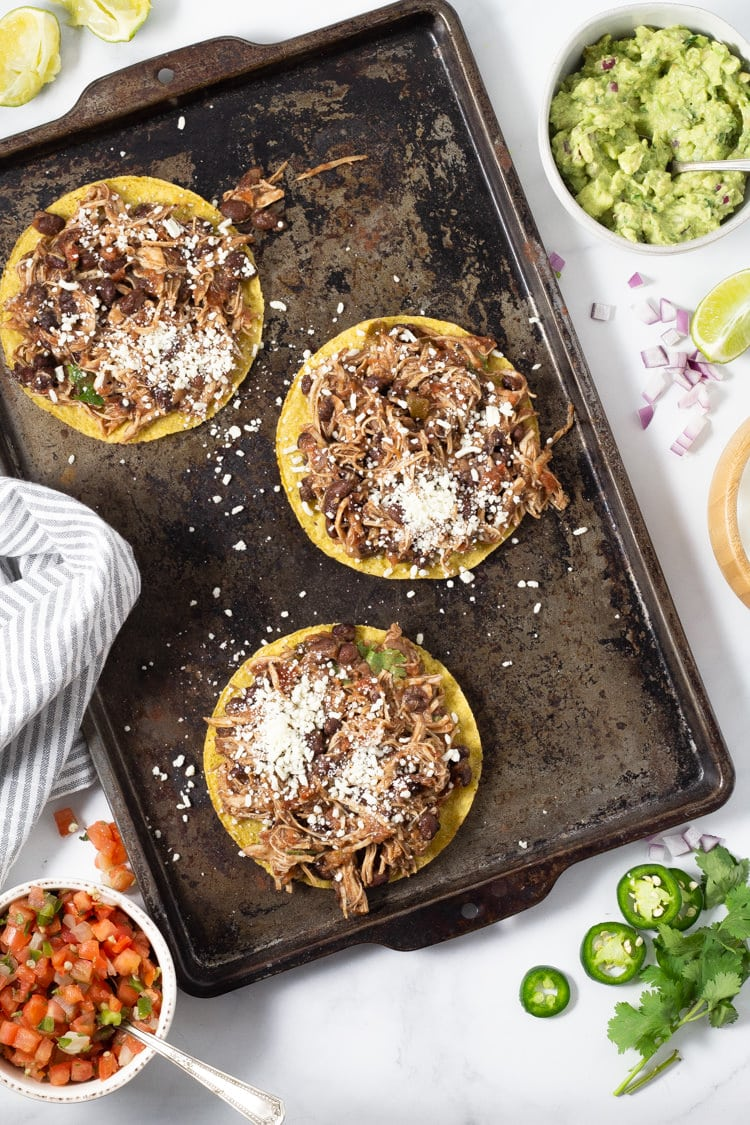 Overhead shot of chicken tostadas during assembly with shredded chicken and crumbled cotija cheese