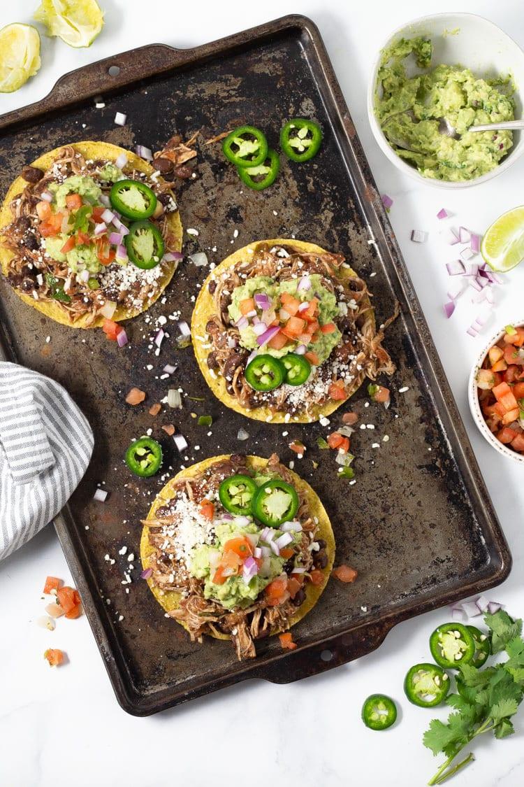 Overhead shot of chicken tostadas topped with guacamole, pico de gallo and sliced jalapeno