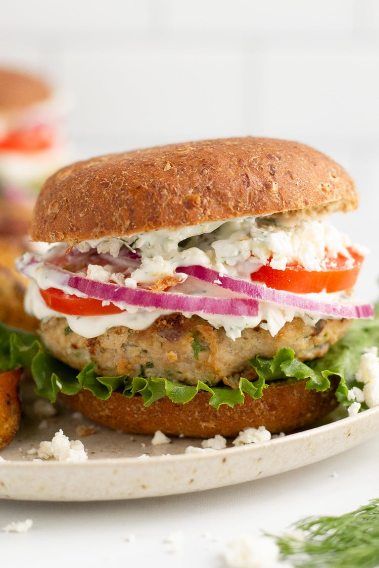Straight on photo of a Greek turkey burger on a wheat bun topped with lettuce, feta, tomato, red onion and tzatziki