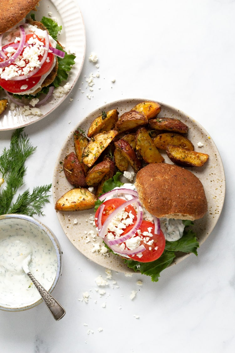 Overhead shot of a plate with a Greek turkey burger and potato wedges
