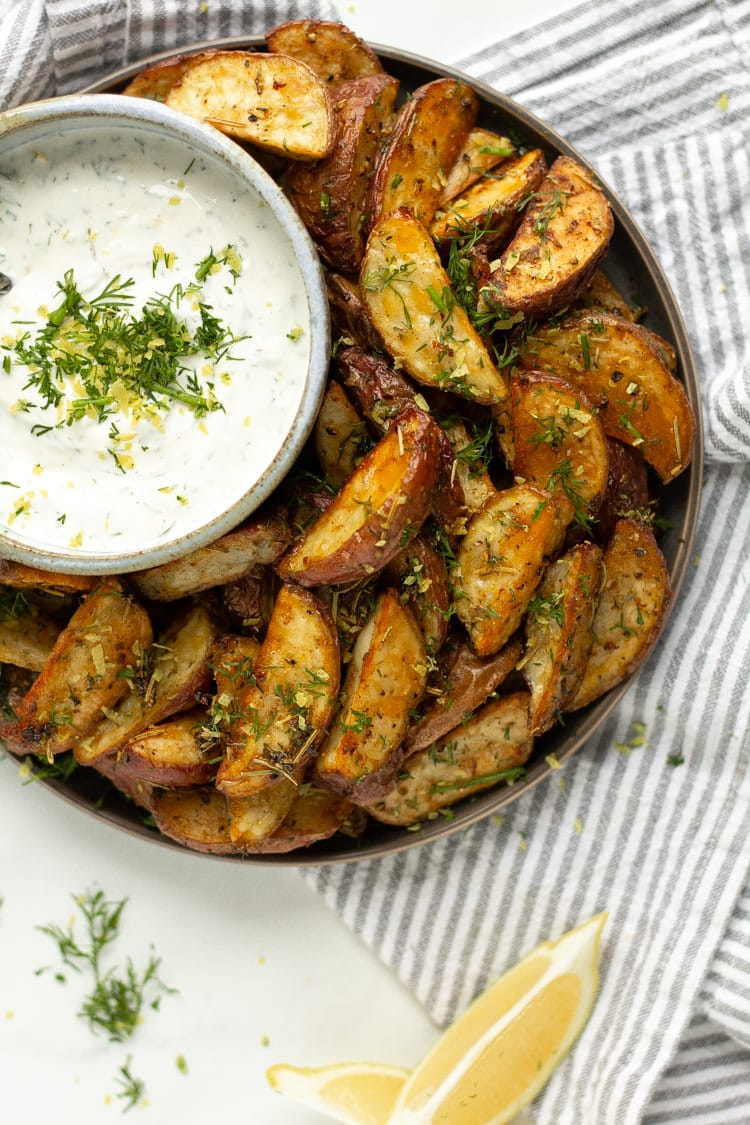 Overhead shot of plate filled with Greek Potato Wedges served with Tzatziki Sauce