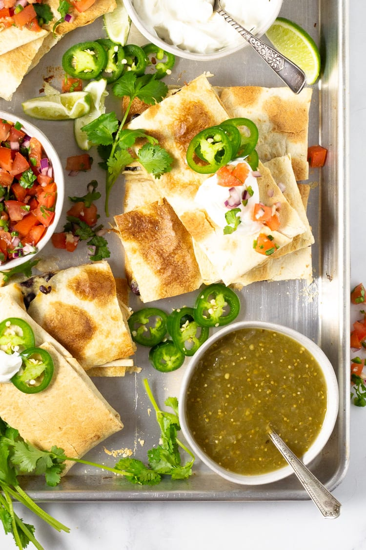 Platter of sheet pan quesadillas garnished with pico de gallo and jalapenos