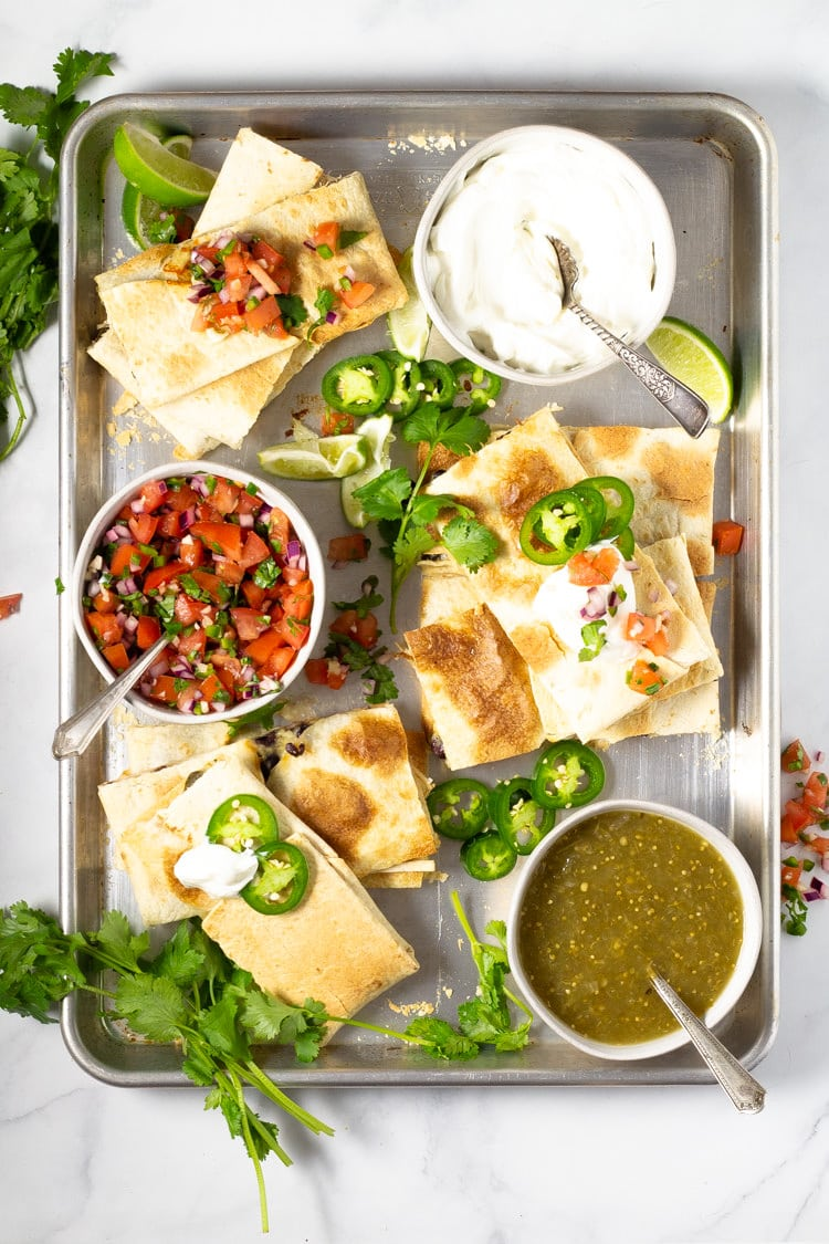 Sheet pan quesadillas garnished with cilantro and jalapenos