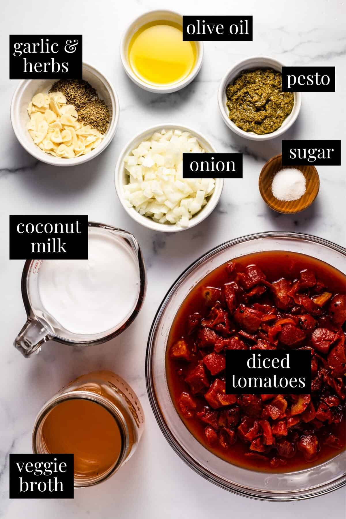 White marble counter top with ingredients to make creamy vegan tomato soup
