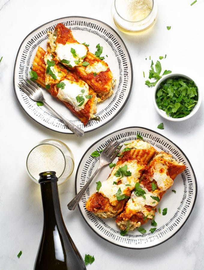 Two plates with baked manicotti