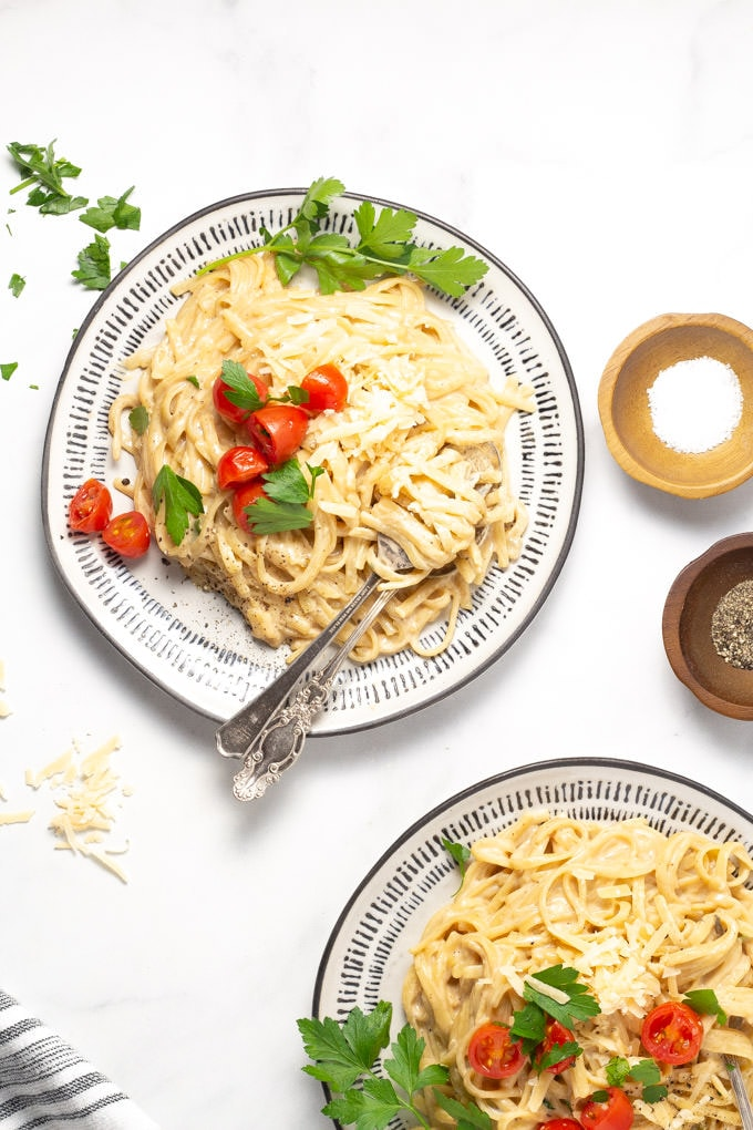 Two plates of fettuccine alfredo garnished with fresh parsley