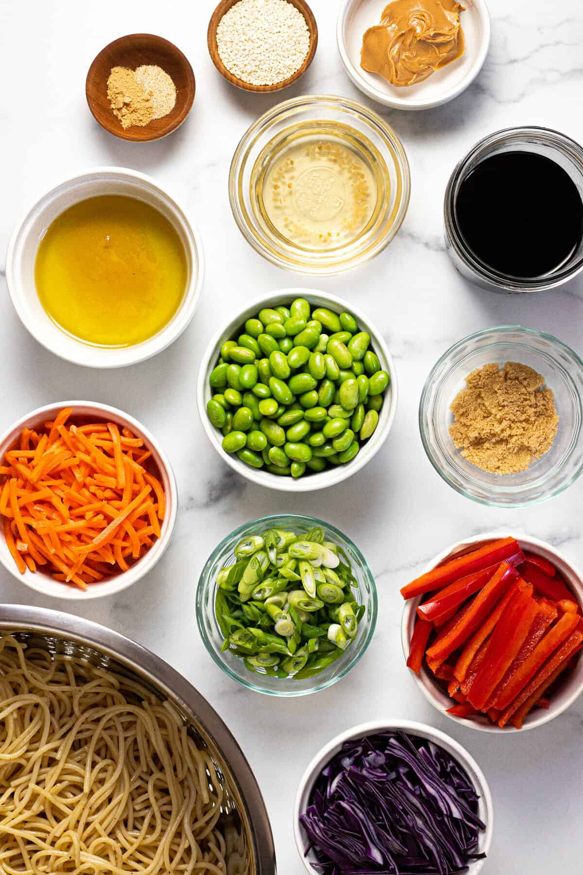 White marble counter top with ingredients to make sesame noodle salad