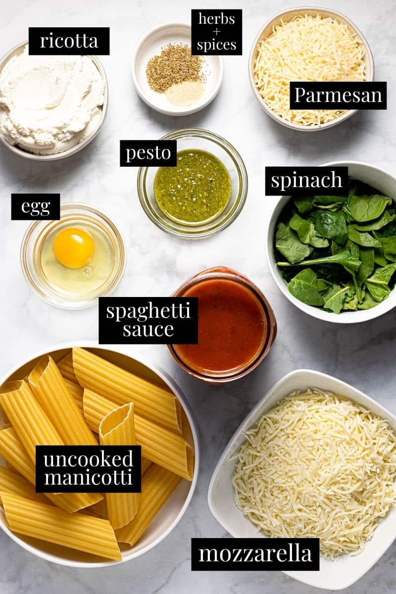 White marble counter top filled with ingredients to make homemade manicotti
