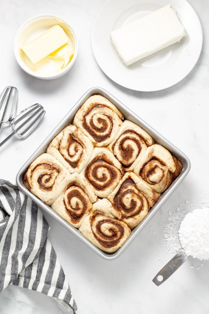 Overhead shot of cinnamon rolls rising in a pan