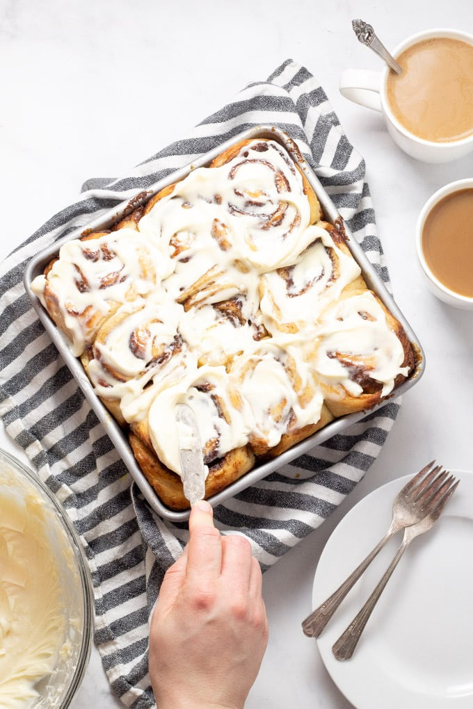 Overhead shot of cinnamon rolls being frosted with cream cheese frosting