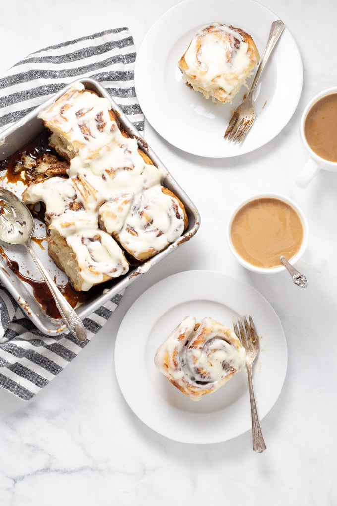 Overhead shot of a table with a pan of cinnamon rolls and two white plates and cups filled with coffee