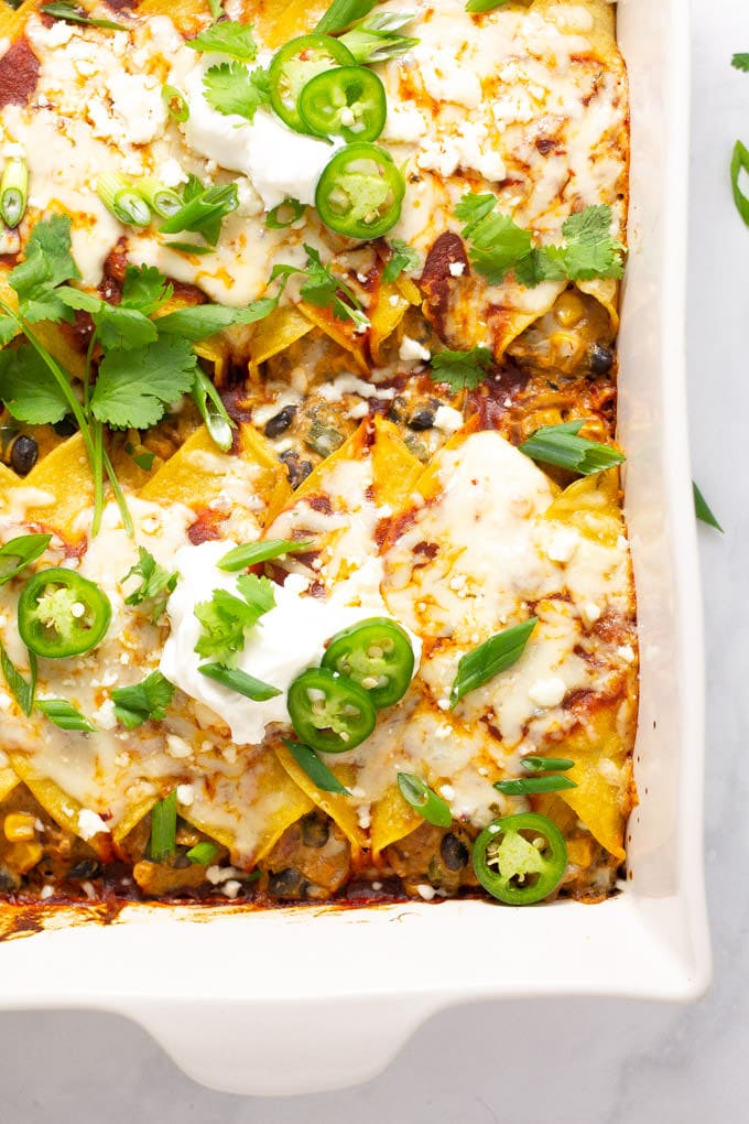 Overhead shot of a pan of veggie enchiladas garnished with jalapeno and cilantro