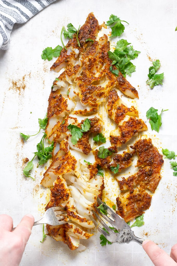 A parchment lined baking sheet with a baked fish fillet on it