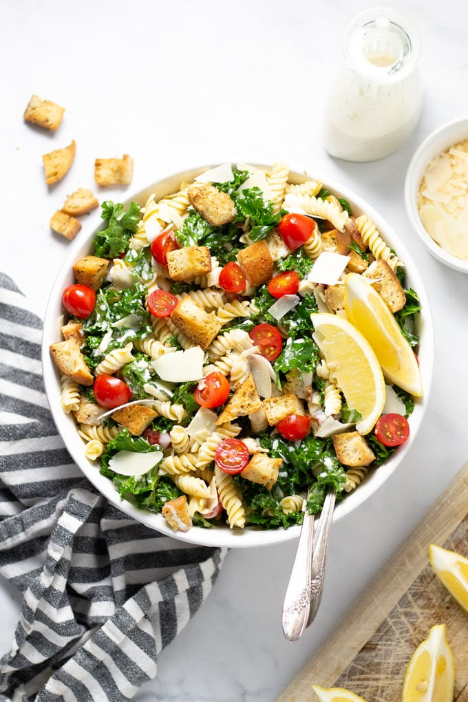 White bowl filled with Kale Caesar Pasta Salad garnished with fresh Parmesan cheese
