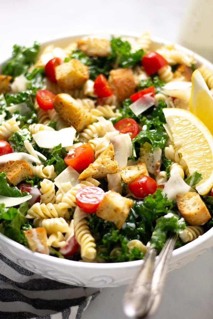 Close up shot of Kale Caesar Pasta Salad garnished with lemon wedges and Parmesan cheese
