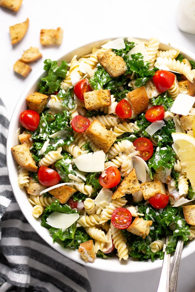Overhead shot of Kale Caesar Pasta Salad garnished with lemon wedges and Parmesan cheese