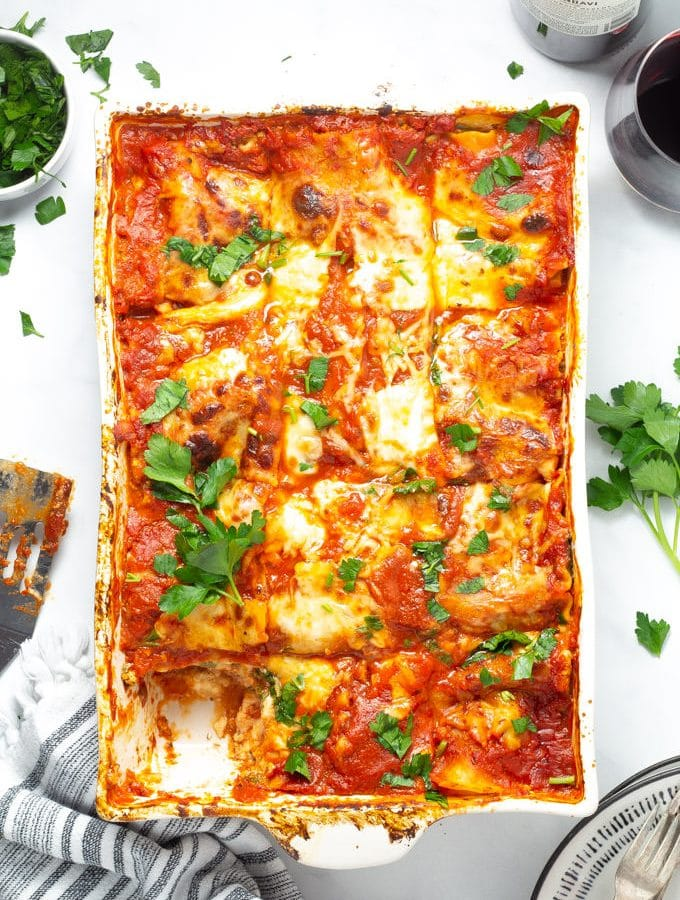 Overhead shot of a pan of homemade lasagna garnished with fresh parsley