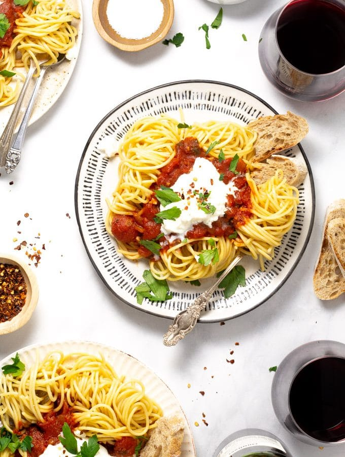 Overhead shot of three plates of spaghetti with homemade pasta sauce and fresh parsley