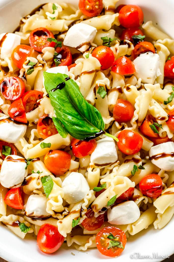 Overhead shot of a white bowl filled with caprese pasta salad drizzled with balsamic reduction