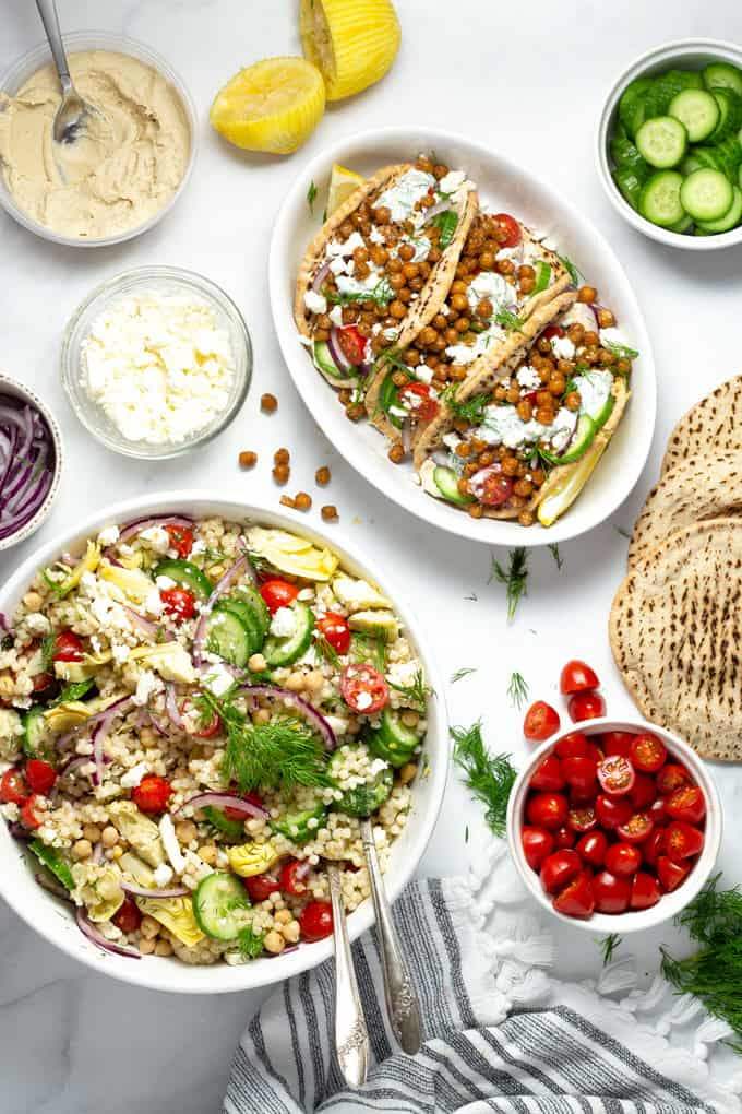 White marble table with a bowl of Mediterranean couscous salad and chickpea gyros along with hummus feta and sliced cucumbers