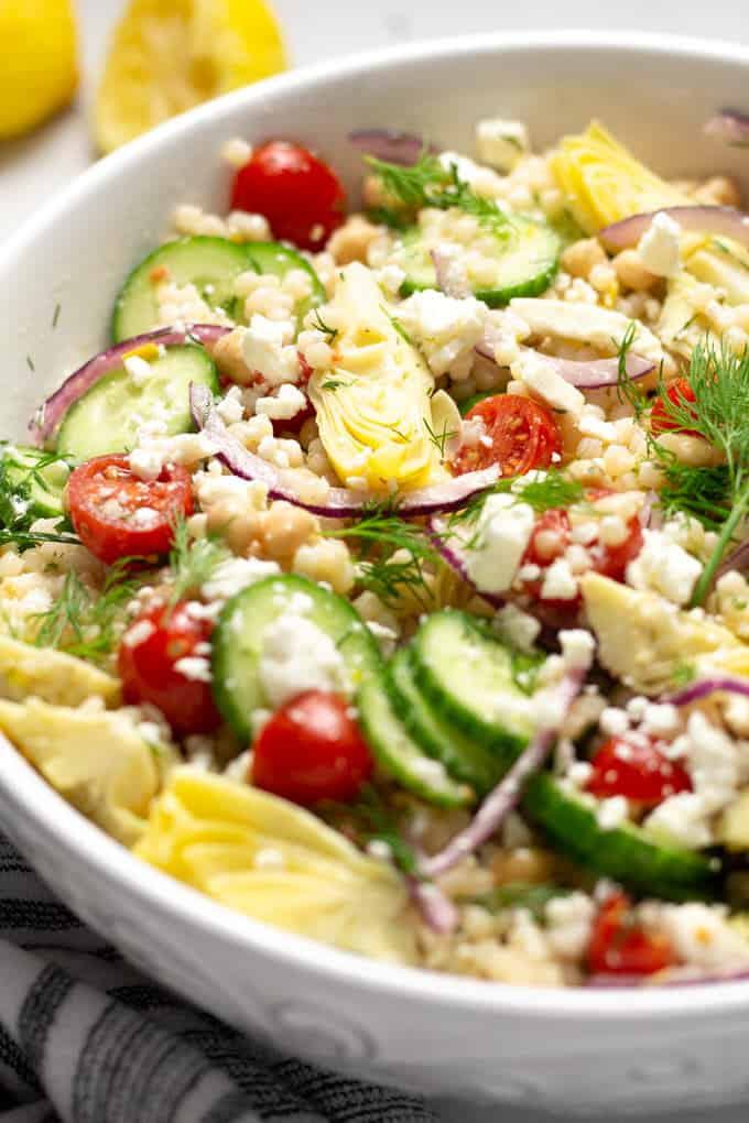 Close up shot of a white bowl filled with mediterranean couscous salad