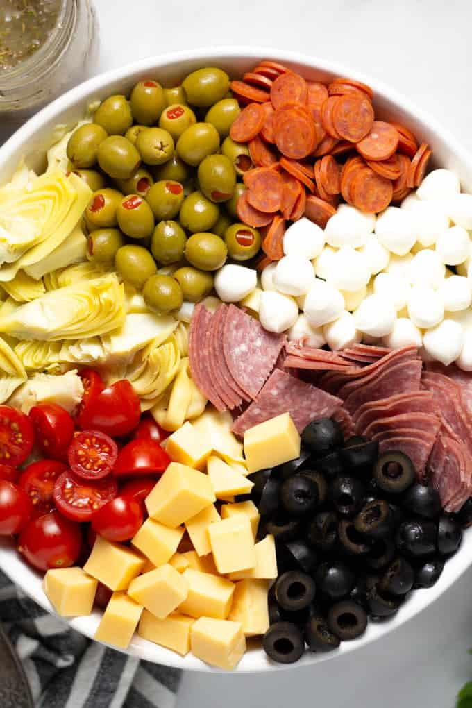 Overhead shot of a white bowl filled with the ingredients for antipasto pasta salad