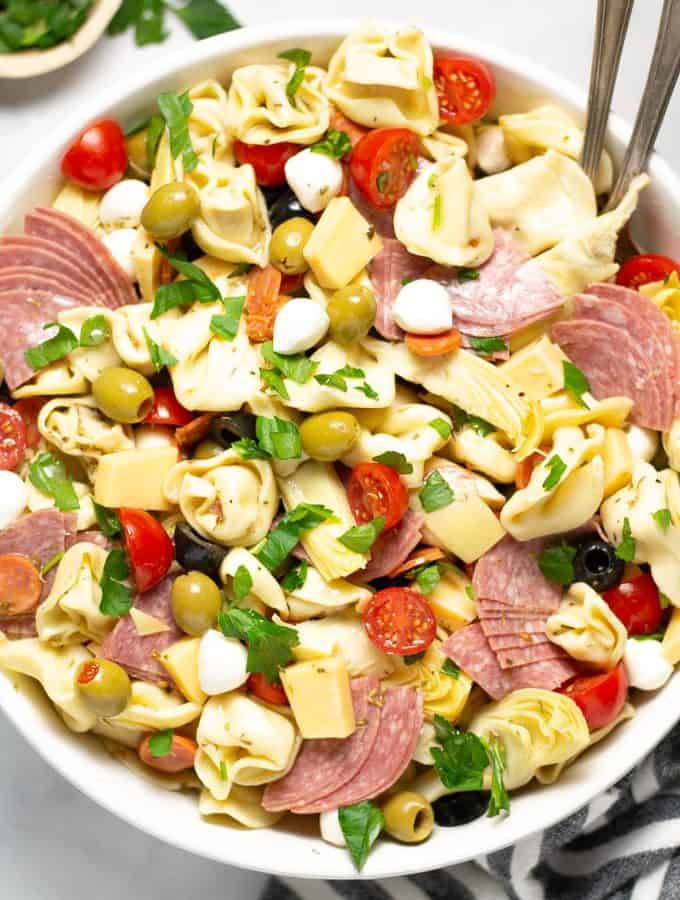 Close up shot of a white bowl filled with antipasto pasta salad