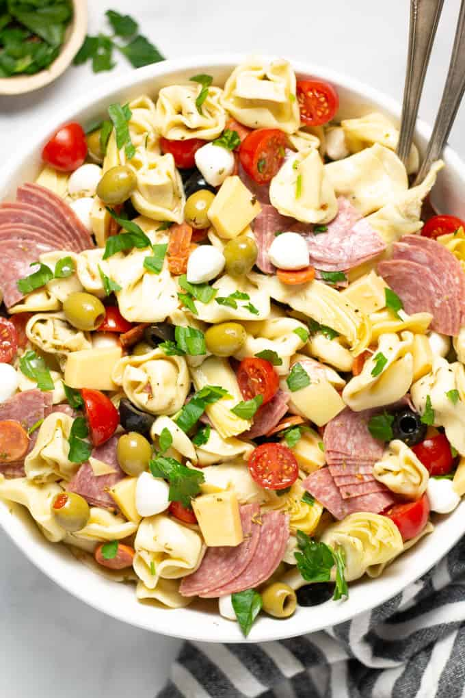 Close up shot of a white bowl filled with pasta salad loaded with meat and veggies