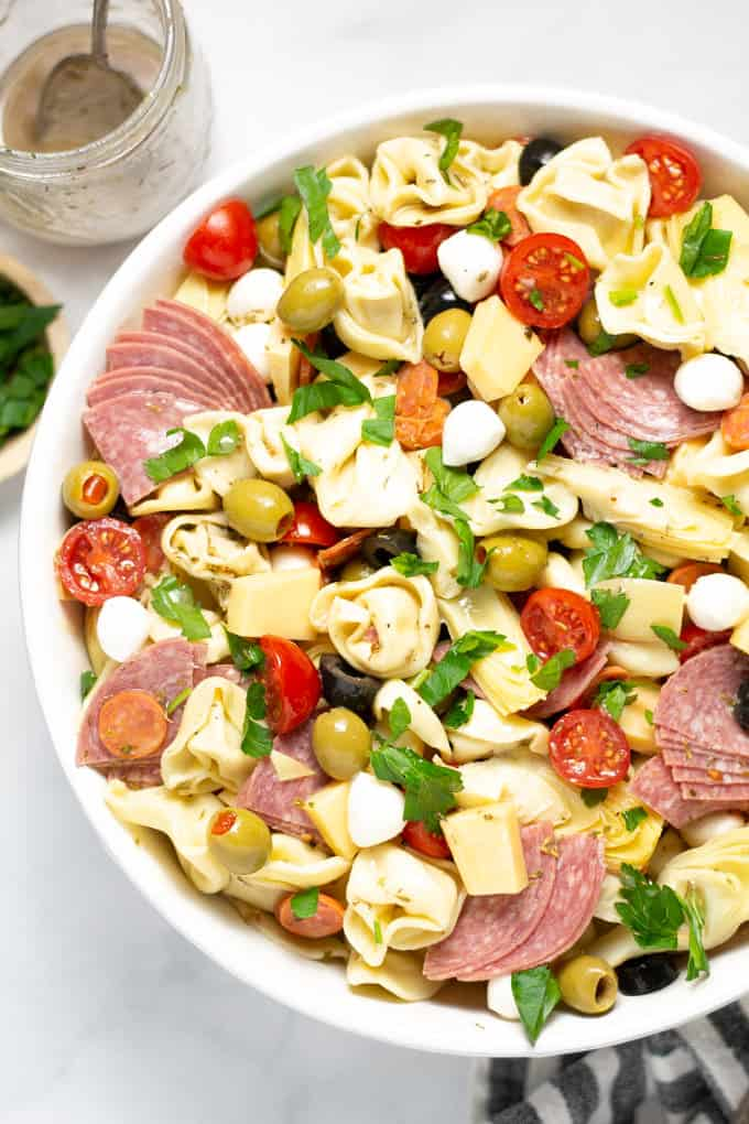 Overhead shot of  a white bowl filled with antipasto pasta salad garnished with fresh parsley
