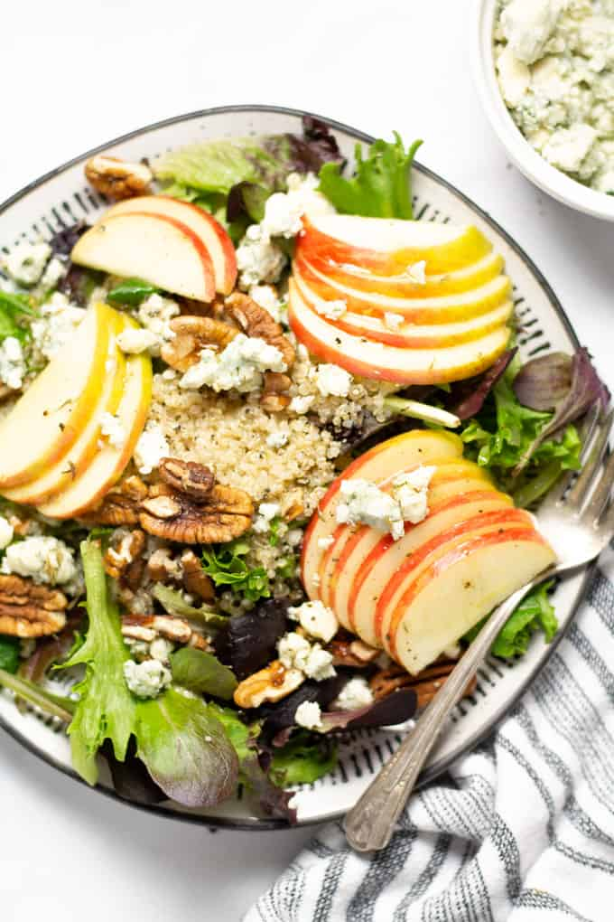 Close up shot of a meal prep salad filled with apple pecan and Gorgonzola on a bed of greens