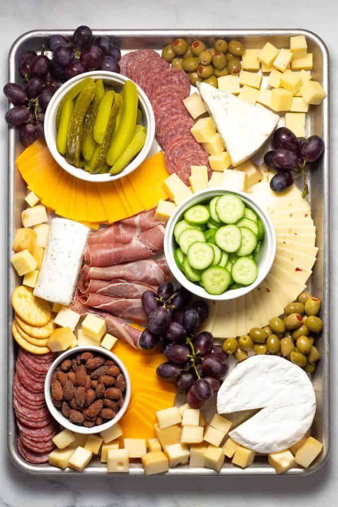 Overhead shot of a cheese board filled with cheese meat veggies and fruit