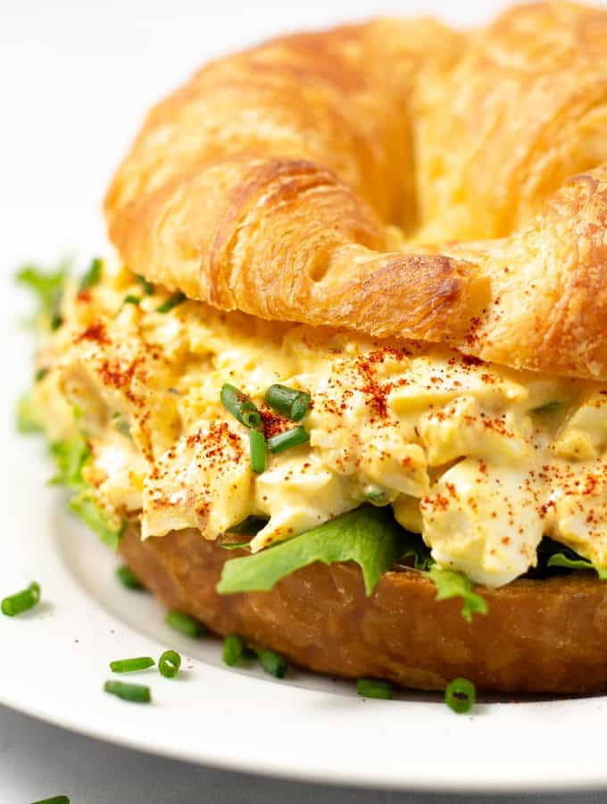 Close up photo of a croissant loaded with deviled egg salad