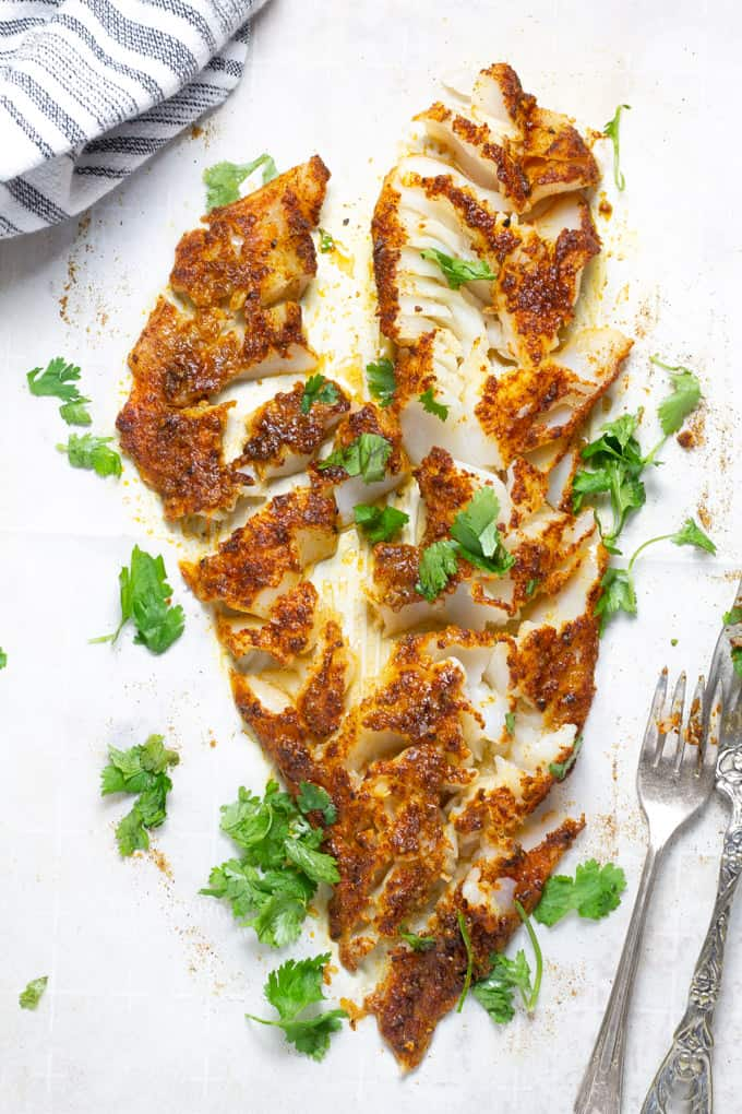A large fish fillet on a parchment lined baking sheet after being flaked with two forks