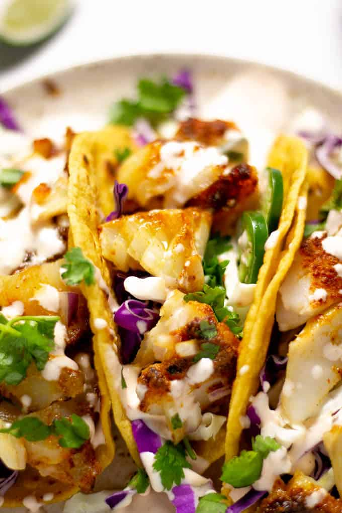 Close up of a plate filled with fish tacos drizzled with chipotle lime sauce