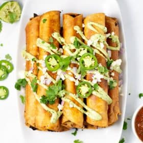 Overhead shot of flautas on a white serving platter
