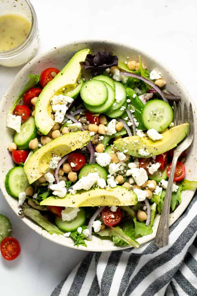 Overhead shot of a meal prep salad loaded with avocado cucumber red onion and tomatoes