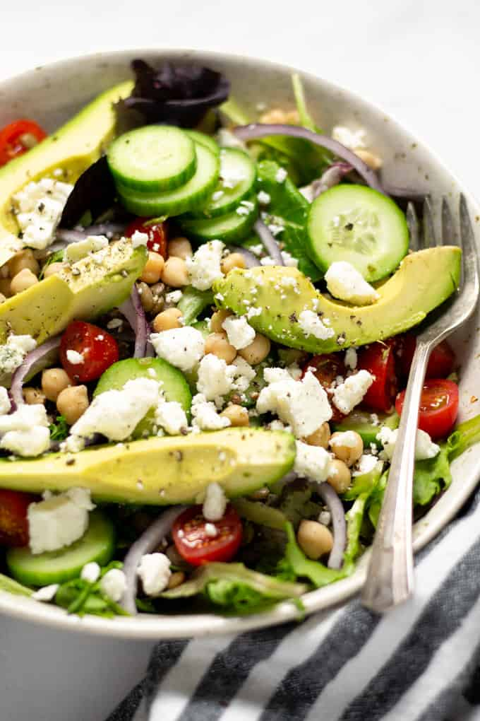 Close up shot of a bowl filled with Greek salad topped with feta cheese