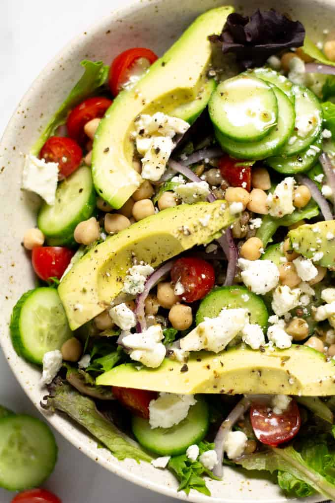 Overhead shot of a bowl filled with Greek salad topped with feta cheese