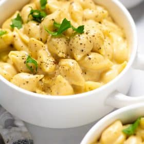 Close up shot of a white bowl filled with macaroni and cheese