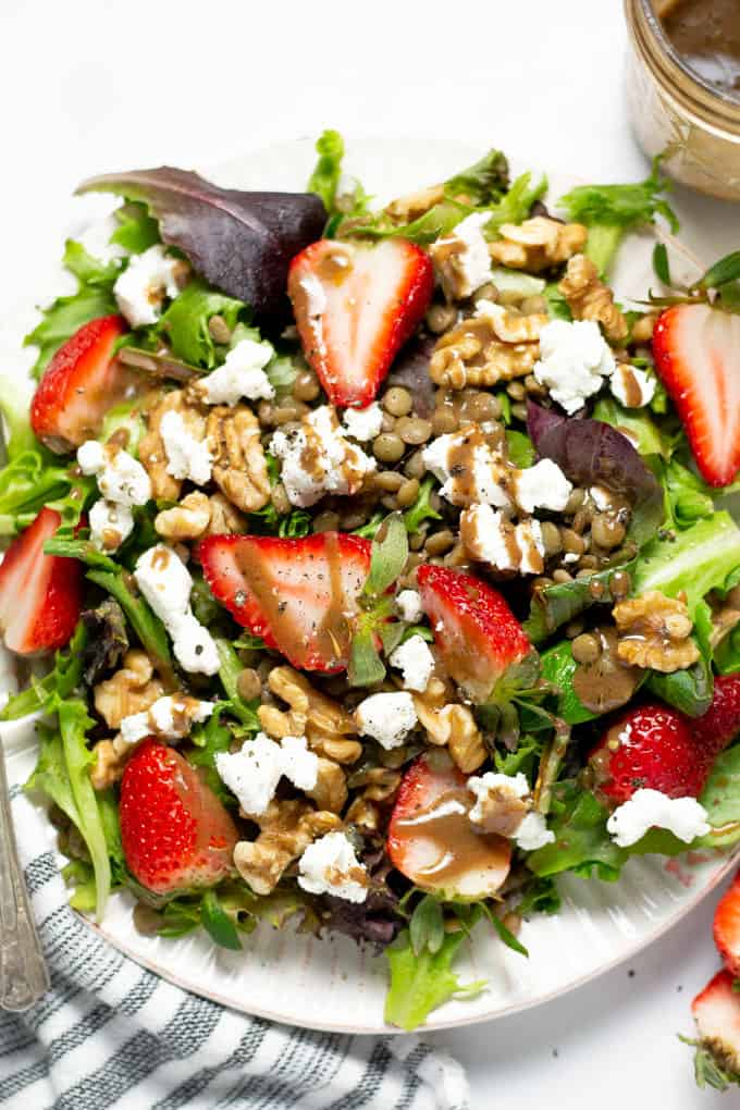 Close up shot of a strawberry salad with goat cheese and balsamic vinaigrette