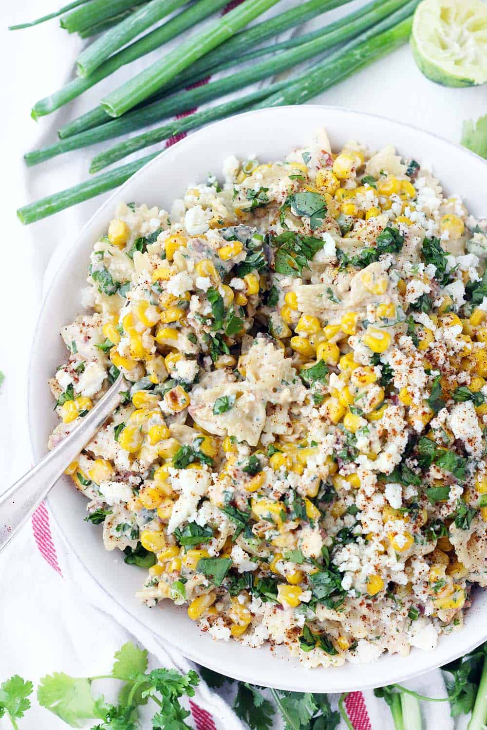 Overhead shot of Mexican corn salad garnished with fresh parsley and paprika