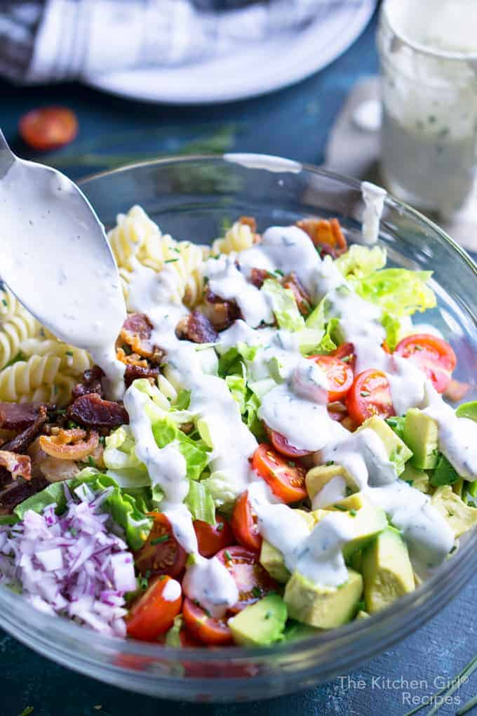 Close up shot of a BLT salad being drizzled with creamy dressing