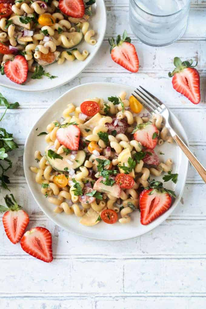 Overhead shot of a white plate filled with strawberry balsamic pasta salad