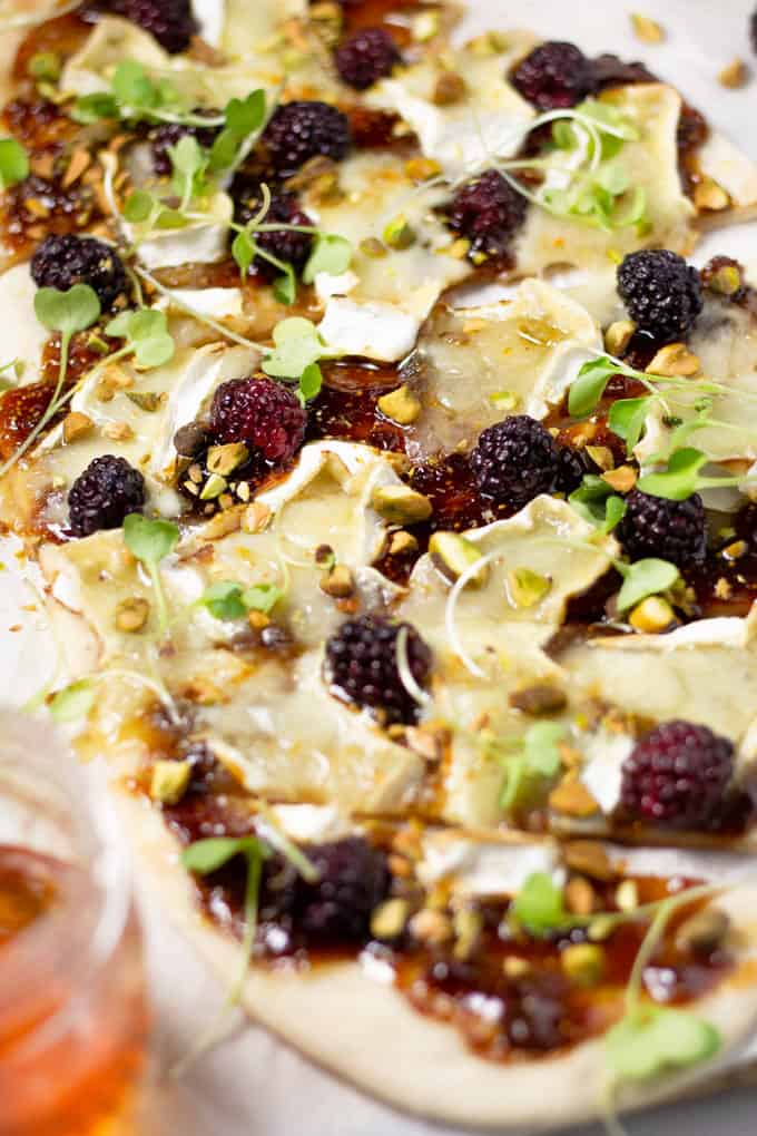 Close up shot of a brie and blackberry flatbread pizza garnished with microgreens
