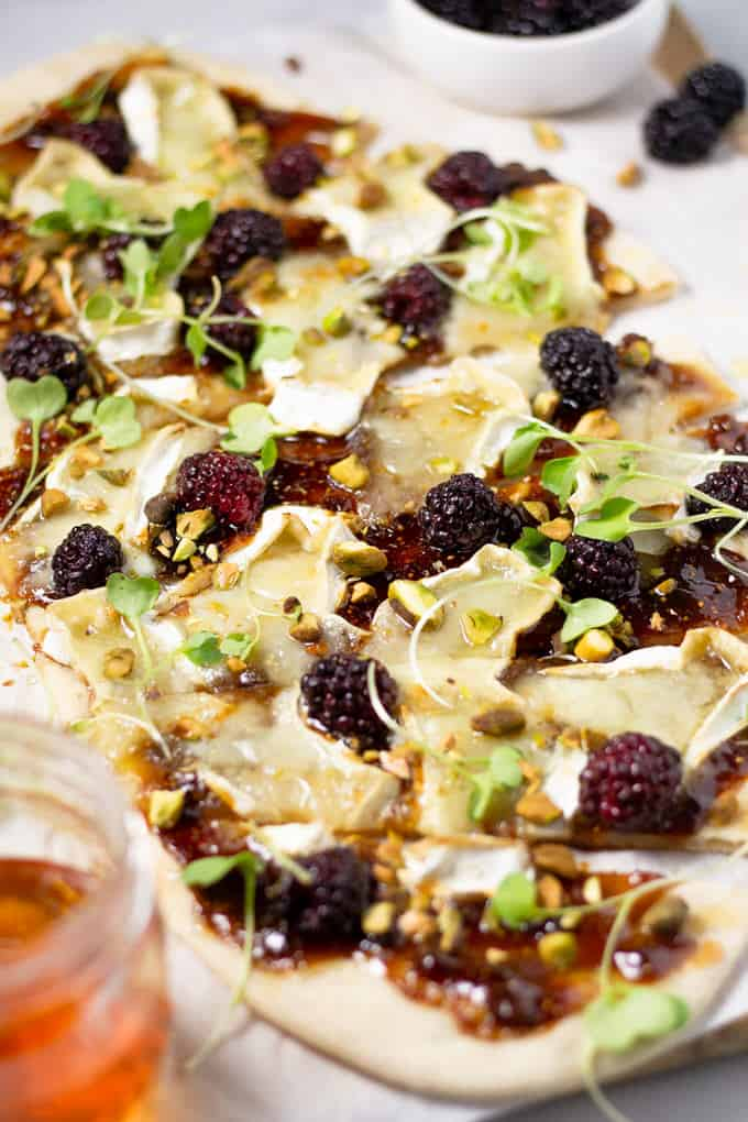 Close up shot of a brie and blackberry flatbread on a cutting board garnished with microgreens